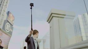 De jonge mens neemt selfies door een selfiestok te gebruiken terwijl achteruit het lopen stock video