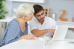 De jonge mens onderwijst grootmoeder om computer te gebruiken stock afbeeldingen