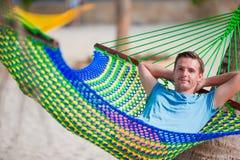 De jonge mens ontspant in hangmat stock afbeelding