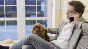 De jonge mens ontspant thuis op bank die op de telefoon en de slagen zijn hond spreken