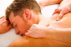 De jonge mens ontvangt massages aan de schouders stock fotografie