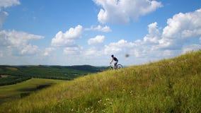 De jonge mens op een fiets rolt neer van een groene heuvel tegen een hemel met wolken stock videobeelden