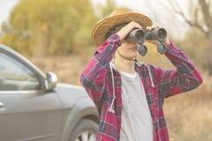 De jonge mens op een wegreis met auto binoculair gebruiken en zoekt de manier F stock foto