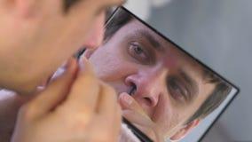 De jonge mens plukt zijn haren thuis van de neus met pincet voor de spiegel stock video