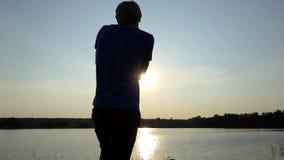 De jonge mens probeert om een gouden sunpath bij zonsondergang in slo-mo te schieten stock videobeelden