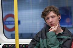De jonge mens reist ondergronds in Londen Stock Foto's