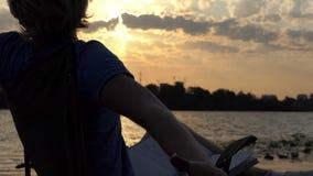 De jonge Mens rekt zich uit n een Vouwende Stoel op Riverbank, bij Zonsondergang schrijft stock videobeelden