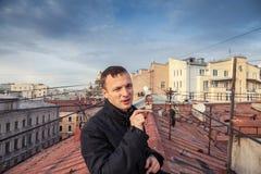 De jonge mens rookt sigaar op het dak in St. Petersburg Stock Foto's