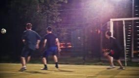 De jonge mens schopt een bal die voorbij andere voetbalsters en voorbij de poort vliegt, nacht die voetbalspel schieten stock videobeelden