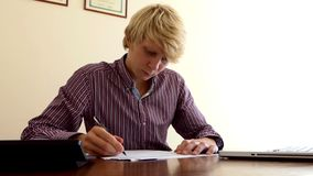 De jonge Mens schrijft een Document, bekijkt Zijn Calculator en een PC in Zijn Bureau stock videobeelden