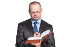 De jonge mens schrijft iets in de agenda royalty-vrije stock afbeelding