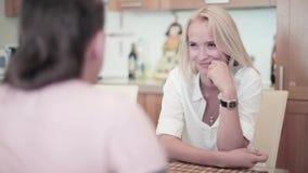 De jonge mens sluit zich aan bij leuk blondemeisje gekleed in witte zitting bij lijst in keuken stock videobeelden