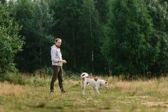 De jonge mens speelt met zijn hond bij aard Stock Foto