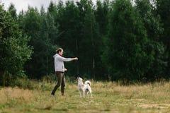 De jonge mens speelt met zijn hond bij aard Stock Fotografie