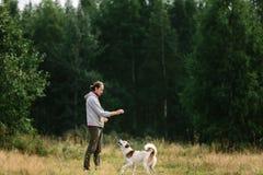 De jonge mens speelt met zijn hond bij aard Royalty-vrije Stock Foto