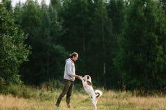 De jonge mens speelt met zijn hond bij aard Stock Afbeeldingen