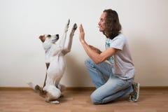 De jonge mens speelt thuis met zijn hond Stock Foto