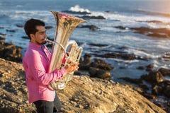 De jonge mens speelt de trompet op rotsachtige overzeese kust royalty-vrije stock afbeelding
