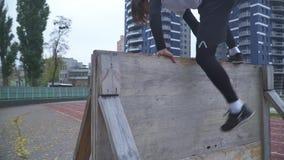 De jonge mens in sportkleding overwint een hindernis in de sportterrein Lopende atleet overwint een hindernis die lopen met stock videobeelden