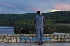 De jonge mens in sportkostuum bij middeleeuws kasteel bekijkt meer en voor Stock Foto's