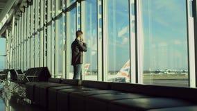 De jonge mens spreekt over een cellphone in luchthaven van Londen en kijkt op de vliegtuigen stock videobeelden