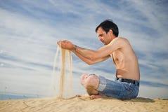 De jonge mens spreidt zand uit Stock Foto