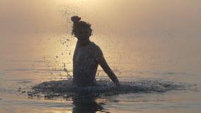De jonge mens springt uit een meer met een dreun op gebaar in slo-mo stock footage