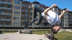 De jonge mens springt volledige ommekeer van bank op de straat stock video