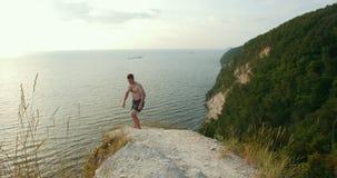 De jonge mens staat van de rand van een klip en het lopen vooruit aan bos op stock video