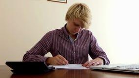 De jonge mens stelt één of ander document samen en bekijkt zijn calculator in bureau stock video