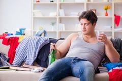De jonge mens student gedronken het drinken alcohol in een slordige ruimte stock fotografie