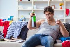 De jonge mens student gedronken het drinken alcohol in een slordige ruimte royalty-vrije stock afbeeldingen
