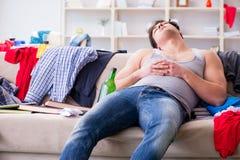 De jonge mens student gedronken het drinken alcohol in een slordige ruimte royalty-vrije stock afbeelding