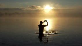 De jonge mens toont een liefdeteken in een meer bij zonsondergang in slo-mo stock videobeelden