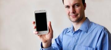 De jonge mens toont slimme telefoon in rechts Royalty-vrije Stock Afbeelding