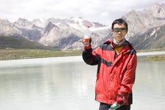 De jonge mens toont waterfles in aard Stock Fotografie