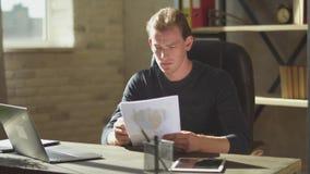 De jonge mens van bedrijfszitting in het bureau bij de lijst dichtbij notitieboekje en het werken bij documenten, maakt binnen am stock videobeelden