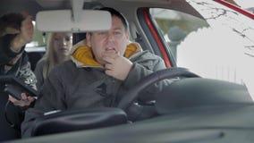 De jonge mens van de achterbank probeert om met de gps navigatie te helpen stock video