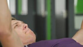 De jonge mens van de sportenbodybuilder de harde training van opleidingsspieren in gymnastiek stock videobeelden