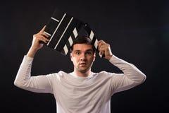 De jonge mens van Kaukasische verschijning houdt een clapperboard Por royalty-vrije stock fotografie
