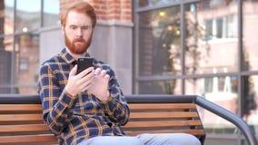 De Jonge Mens van de roodharigebaard het Typen Bericht op Smartphone, Zitten Openlucht op bank stock footage