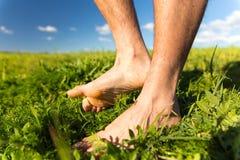 De jonge mens verdraaide blootvoets voeten op groen gras Royalty-vrije Stock Afbeeldingen