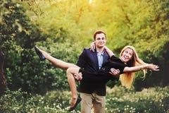 De jonge mens vervoert haar meisje op handen Royalty-vrije Stock Fotografie