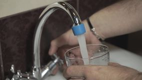 De jonge mens verzamelt een glas water van de kraan stock video