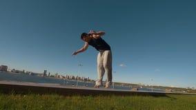 De jonge mens voert acrobatische tik op de rand die van een klip uit de rivier en cityscape overzien stock video