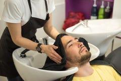 De jonge mens wast zijn hoofd in een herenkapper Royalty-vrije Stock Foto