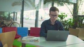 De jonge mens werkt met laptop in de bibliotheek stock video