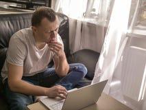 De jonge mens werkt met laptop terwijl thuis het zitten stock foto