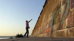De jonge mens werpt een bal op een steenachtige muur van een rivierbank in slo-mo stock videobeelden