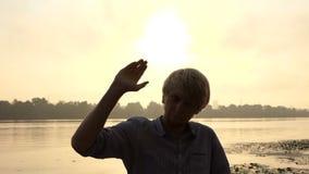 De jonge Mens werpt Zijn Hand vooruit, geniet van het Leven, op een Riverbank in slo-Mo stock videobeelden